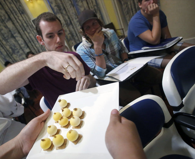 "In this Thursday, February 19, 2015 photo, Participants at a Cordon Bleu cooking school seminar in Bangkok try a ""Bamboo Worm Bite"", a dessert that uses bamboo worms and stink bugs as ingredients. (Photo by Sakchai Lalit/AP Photo)"