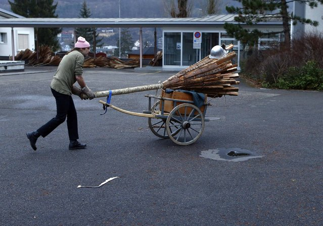 A carnival reveller transports wooden sticks before he takes part in the traditional Swiss Chienbaese celebration in Liestal near Basel February 22, 2015. (Photo by Ruben Sprich/Reuters)