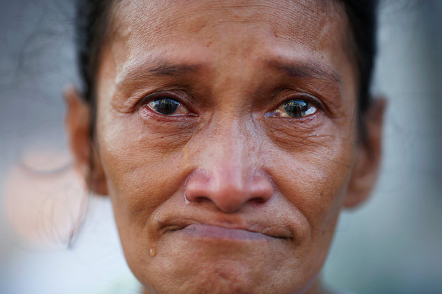 The mother of Angelo Lafuente, whose body, riddled with bullets, was found by a filthy river that feeds into the Manila bay, cries as she visits his grave on the All Saints Day in Manila, Philippines November1, 2016. (Photo by Damir Sagolj/Reuters)