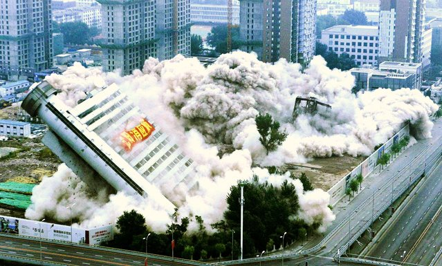 The Liaoning Province Meteorological Station building topples near a residential construction site during a controlled demolition in Shenyang, China, on September 29, 2013. The building, with a 45-meter-high giant thermometer attached to its exterior, was demolished to make way for a new residential area. (Photo by Reuters)
