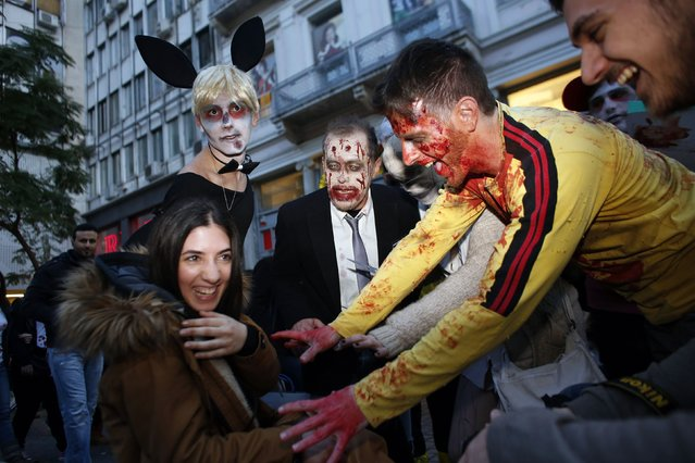 Revellers dressed as zombies interact with pedestrians during an annual zombie walk in Athens, February 21, 2015. (Photo by Kostas Tsironis/Reuters)