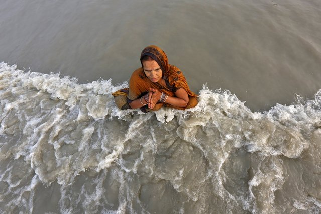 "A Hindu pilgrim offers prayers after taking a dip at the confluence of the river Ganges and the Bay of Bengal, ahead of the ""Makar Sankranti"" festival at Sagar Island, south of Kolkata, India, January 13, 2016. (Photo by Rupak De Chowdhuri/Reuters)"