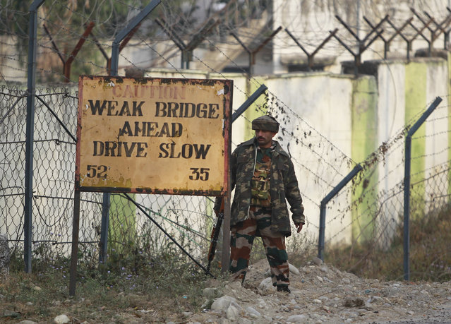 An Indian soldier takes position outside an army camp at Nagrota, in the outskirts of Jammu, India, Tuesday, November 29, 2016. Police said that militants fired indiscriminately and tried to enter an army camp in Nagrota town, triggering a fierce gun battle. (Photo by Channi Anand/AP Photo)