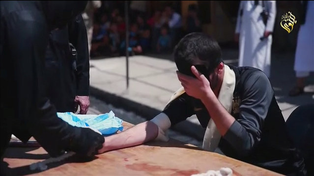 A masked Islamic State militant prepares the hand of a man for public amputation in what is said to be in Al-Karama district, Mosul, Iraq, in this still image taken from video from the Islamic State. (Photo by Reuters TV)