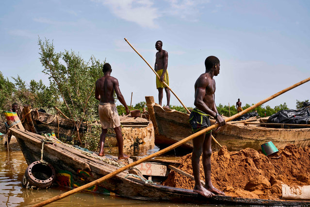 Malian diggers stand on their boats loaded with sand at an extraction site on a affluent of the Niger River near Kangaba, in Mali' s southwestern Koulikoro region, on October 2, 2018. (Photo by Michele Cattani/AFP Photo)
