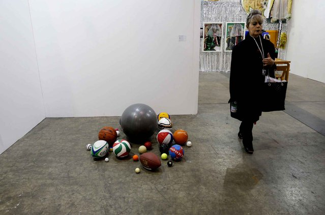 "A woman walks past an artwork ""Balls"" created by British artist and musician Martin Creed during the VIP preview of the art fair Art Basel in Hong Kong Friday, March 13, 2015. (Photo by Kin Cheung/AP Photo)"