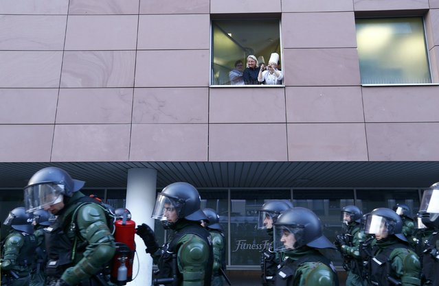 People take pictures of German riot police officers in Frankfurt, March 18, 2015. Anti-capitalist protesters clashed with riot police near the new headquarters of the European Central Bank (ECB) in Frankfurt on Wednesday and set fire to barricades and cars, casting a pall over the ceremonial opening of the billion-euro skyscraper. (Photo by Ralph Orlowski/Reuters)