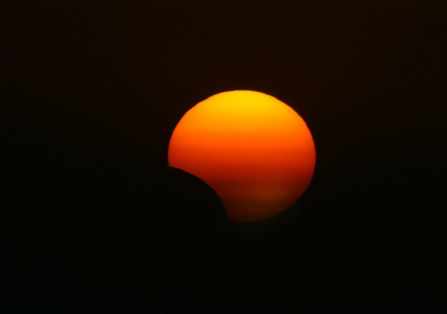 This picture taken on November 3, 2013 shows a rare hybrid solar eclipse, in the northern Iraqi city of Arbil. The rare solar eclipse will sweep across parts of Africa, Europe and the United States as the moon blocks the sun either fully or partially, depending on the location. (Photo by Safin Hamed/AFP Photo)