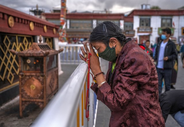 A Tibetan Buddhist woman prays in front of the Jokhang Temple, a UNESCO heritage site, on June 1, 2021 in Lhasa, Tibet Autonomous Region, China. (Photo by Kevin Frayer/Getty Images)