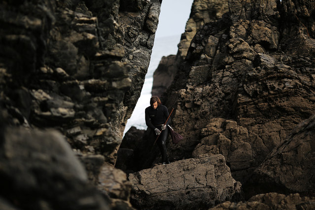 """Santi Diaz Mosquera, 41, a """"percebeiro"""" (barnacle fisherman), walks on rocks after collecting barnacles on the coast of Ferrol, in the northwestern Spanish region of Galicia, December 14, 2016. (Photo by Nacho Doce/Reuters)"""
