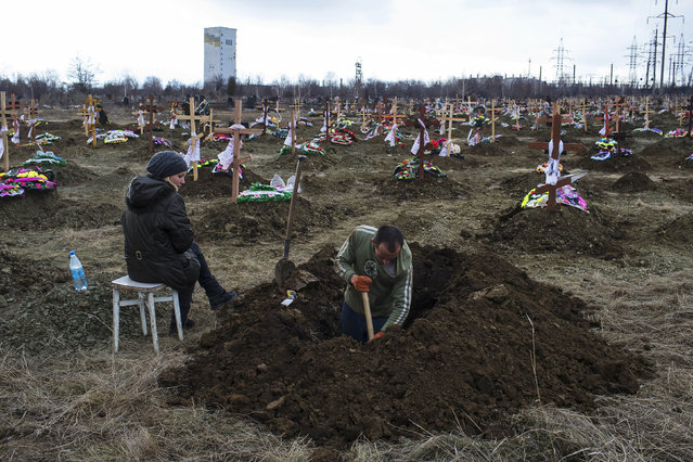 A grave digger works as his wife watches, at a cemetery where workers killed by a blast at the Zasyadko coal mine will be buried, in Donetsk March 5, 2015. (Photo by Marko Djurica/Reuters)