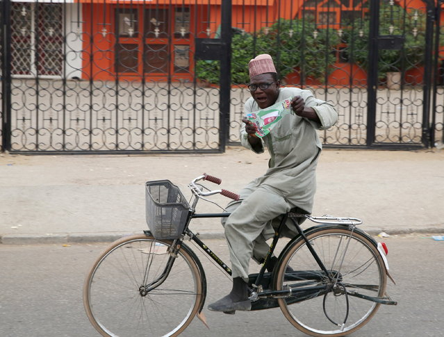 A supporter of the presidential candidate Muhammadu Buhari and his All Progressive Congress (APC) party celebrates on his bicycle in Kano, March 31, 2015. (Photo by Goran Tomasevic/Reuters)