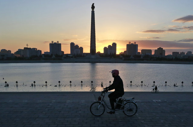 """In this Saturday, October 27, 2018 photo, a man rides his electric bike as the Tower of the Juche Idea is silhouetted agains the sunrise in Pyongyang, North Korea. North Korea is exploring a grand plan to become a regional transportation hub, inspired in part by the successes of Singapore and Switzerland, and would be open to joining world financial institutions such as the International Monetary Fund if current member states give up their """"hostile"""" policies toward it, a senior government economist has told The Associated Press. (Photo by Dita Alangkara/AP Photo)"""