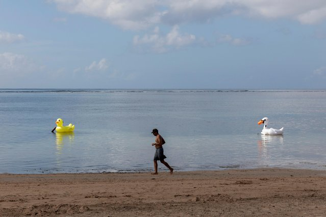 A man run at a beach while Indonesia prepares to impose emergency measures tightening restrictions in Java and Bali as coronavirus disease (COVID-19) cases surge, in Sanur, Bali, Indonesia, July 2, 2021. (Photo by Nyimas Laula/Reuters)