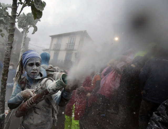 """Revellers participate in a flour fight during the """"O Entroido"""" festival in Laza village Spain February 8, 2016. The carnival lasts for a week and is considered a major social and cultural event in Laza. (Photo by Miguel Vidal/Reuters)"""