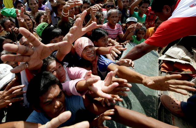 Typhoon survivors jostle to beg for plastic bags of food relief along a road Thursday, November 28, 2013, in Tacloban city, Leyte province in central Philippines.  Typhoon Haiyan, one of the most powerful storms on record, hit the country's eastern seaboard November 8, leaving a wide swath of destruction. (Photo by Bullit Marquez/AP Photo)