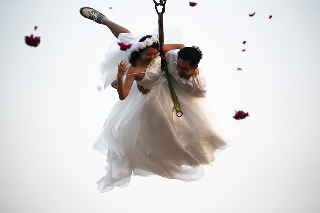 Bride Duangreuthai Amnuayweroj and groom Kasemsak Jiranantiporn fly while attached to cables during a wedding ceremony ahead of Valentine's Day at a resort in Ratchaburi province, Thailand, February 13, 2016. Four Thai couples took part in the wedding ceremony arranged by the resort. (Photo by Athit Perawongmetha/Reuters)