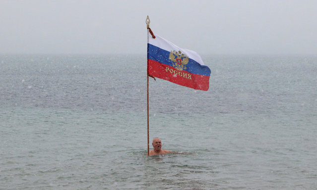 A fan of winter swimming holds a Russian flag during a festive event marking Orthodox Christmas in the Black Sea port of Yevpatoriya, Crimea January 7, 2019. (Photo by Pavel Rebrov/Reuters)