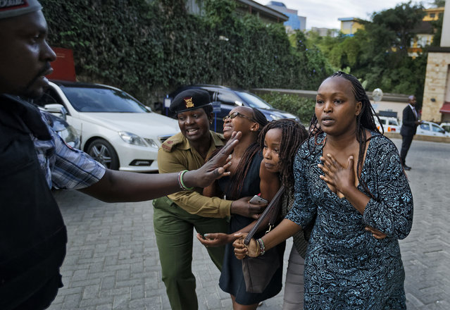 Civilians flee helped by a member of the security forces at a hotel complex in Nairobi, Kenya, Tuesday, January 15, 2019. Terrorists attacked an upscale hotel complex in Kenya's capital Tuesday, sending people fleeing in panic as explosions and heavy gunfire reverberated through the neighborhood. (Photo by Ben Curtis/AP Photo)