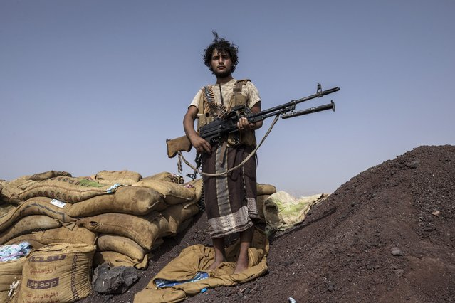 Yemeni fighter Hassan Saleh backed by the Saudi-led coalition stands for a photograph after clashes with Houthi rebels on the Kassara front line near Marib, Yemen, Sunday, June 20, 2021. Saleh and his younger brother Saeed, both in their early 20s, both in their early 20s, have been fighting alongside other government fighters and tribesman outside the oil-rich city of Marib against the months-long offensive by the Iranian-backed rebels. They say they need more weapons to push the attackers back. (Photo by Nariman El-Mofty/AP Photo)