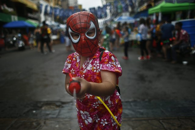 "A kid with ""Spiderman"" mask sprays water with water gun in the middle of a water fight as Thais and foreign tourists celebrate the water festival Songkran on the popular tourist strip of Khao San road on the first day of the water festival Songkran celebrations, the Thai traditional New Year, in Bangkok, Thailand, 12 April 2015. (Photo by Fazry Ismail/EPA)"