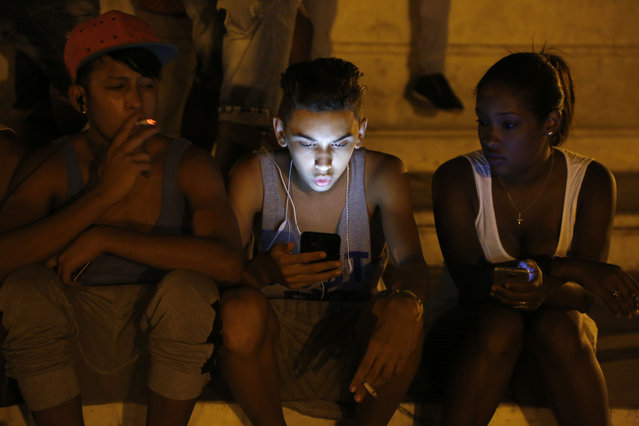 In this July 1, 2015 file photo, youths use a password protected wifi network coming from a five star hotel to surf the Internet on their smart phones in downtown Havana, Cuba. Cuba's government announced on Tuesday, December 4, 2018 that its citizens will be offered full internet access on mobile phones starting Thursday, Dec. 6, becoming one of the last nations to do so. (Photo by Desmond Boylan/AP Photo)