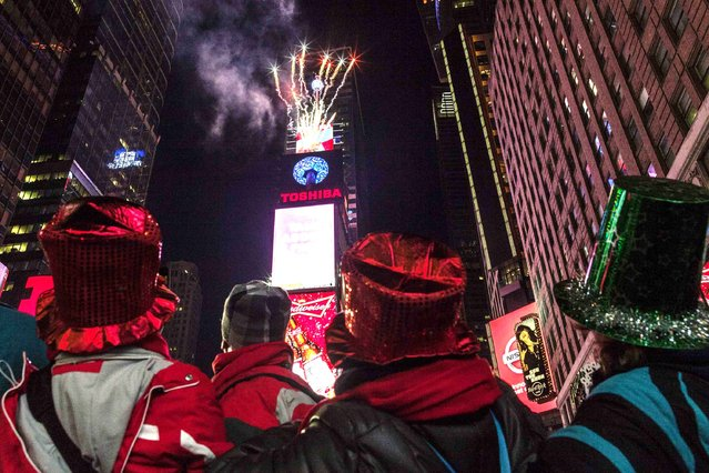 People look towards fireworks exploding from Times Square's New Year's Eve Ball during New Year's Eve celebrations at Times Square in New York, December 31, 2013. (Photo by Zoran Milich/Reuters)