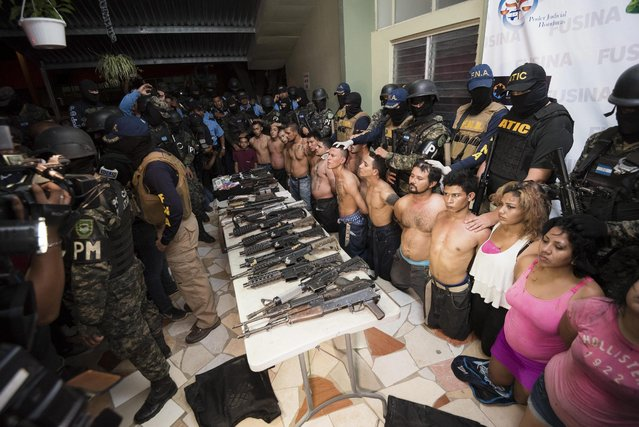 Members of the National Inter-Institutional Security Force (FUSINA) present alleged members of the gang Barrio 18, who were found to be in possession of illegal weapons in San Pedro Sula, Honduras, 18 January 2017. (Photo by Jordan Perdomo/EPA)