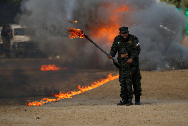 A Palestinian boy uses a torch to burn a mock Israeli army post as part of a drill during a graduation ceremony for members of Palestinian National Security Forces loyal to Hamas, in Gaza City January 22, 2017. (Photo by Suhaib Salem/Reuters)