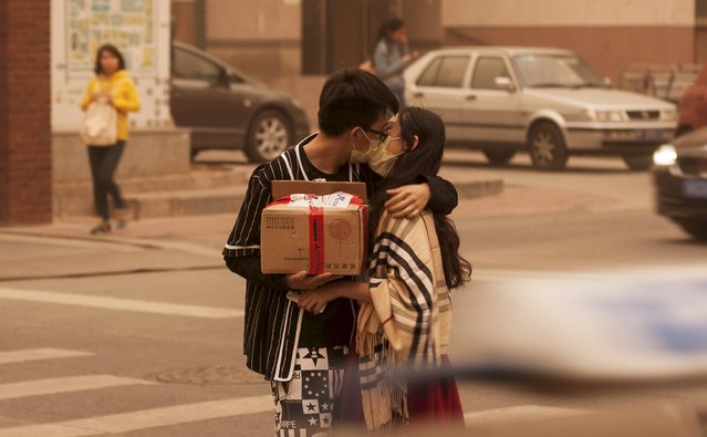 A couple wearing masks kiss along a street during a sandstorm in Beijing, April 15, 2015. (Photo by Reuters/China Daily)