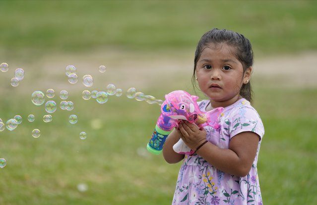 Zoe Olea, 2, plays with bubbles at Echo Park in Los Angeles Monday, August 17, 2020. A heat wave brought triple-digit temperatures and raised wildfire danger and fears of coronavirus spread, a significant concern in a state with more than 621,000 confirmed cases. Public health officers urged people to follow masks and social distancing orders if they head outdoors. (Photo by Damian Dovarganes/AP Photo)
