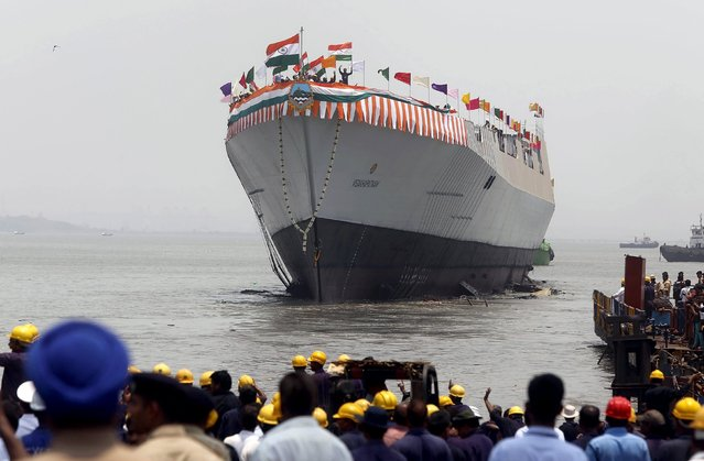 Employees watch as the newly built Indian Naval warship INS Visakhapatnam sails into the Arabian Sea during its launch at Mazagon Docks, a naval vessel ship building yard, in Mumbai April 20, 2015. (Photo by Shailesh Andrade/Reuters)