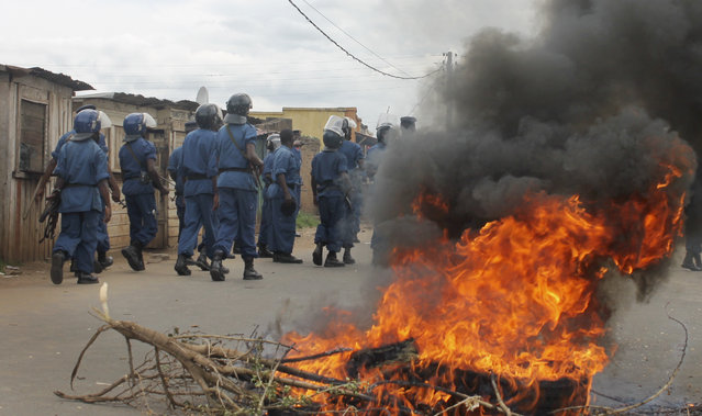Burundian riot police march past a burning tyre roadblock following clashes with opposition protesters in a street in the capital Bujumbura, Burundi Sunday, April 26, 2015. (Photo by Eloge Willy Kaneza/AP Photo)