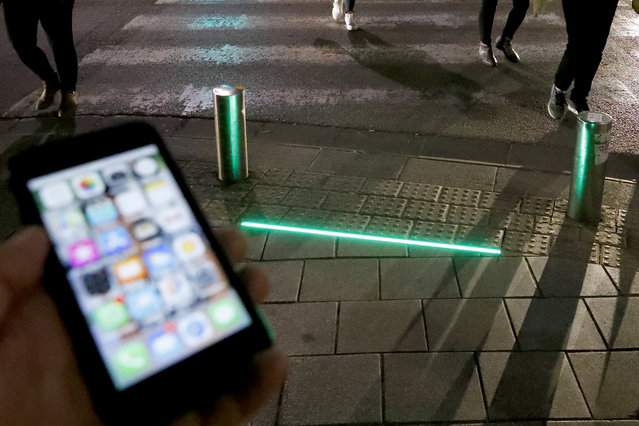 A picture taken on March 12, 2019 shows LED ground level lights installed to warn texting pedestrians before crossing the road in the coastal city of Tel Aviv. (Photo by Jack Guez/AFP Photo)