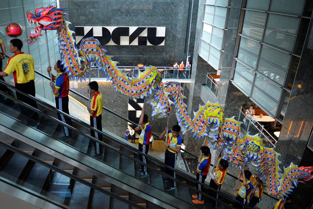 Dragon dance performers ride an escalator to perform at the trading floor of the Philippine Stock Exchange to celebrate the Chinese Lunar New Year of the Rooster in Makati city, Metro Manila, Philippines January 30, 2017. (Photo by Ezra Acayan/Reuters)