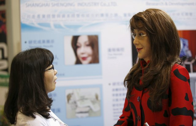 "A woman looks at a humanoid robot named ""Yangyang"" (R) during its demonstration at the Global Mobile Internet Conference (GMIC) 2015 in Beijing, China, April 29, 2015. (Photo by Kim Kyung-Hoon/Reuters)"