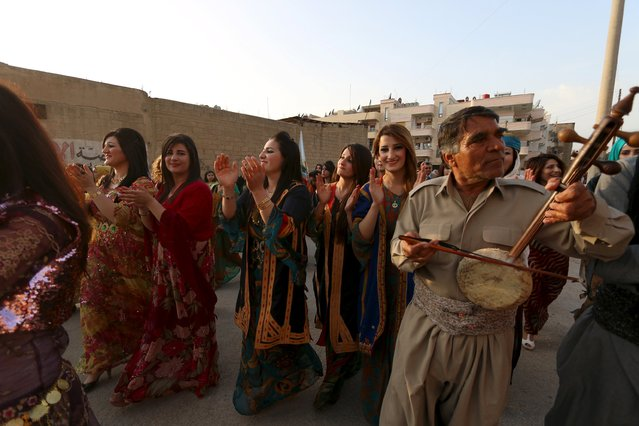 Kurdish women wearing traditional clothes dance during a celebration for Kurdish outfit day in the northeast Syrian Kurdish city of Qamishli Syria March 10, 2016. (Photo by Rodi Said/Reuters)