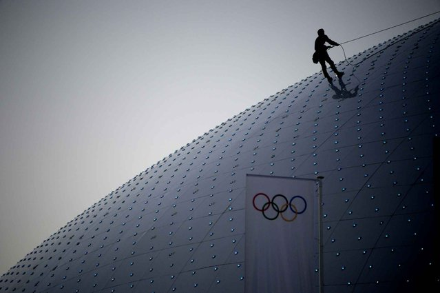 A worker climbs the roof of the Bolshoy ice dome, home to the ice hockey events in the seaside cluster prior to the start of the 2014 Sochi Winter Olympics on February 2, 2014 in Sochi. (Photo by Alexander Nemenov/AFP Photo)