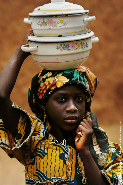A Nigerian girl carries pots on her head in a remote area of Nigeria's Muslim north April 9, 2005 in Rimin Gado, Nigeria.  Polio, a disease that health workers once had hoped to eradicate worldwide by 2005, is on the march again in Nigeria, especially in this region, where local Islamic leaders banned the polio vaccine two years ago over post September 11 suspicions of everything Western. Inoculations have resumed and Nigeria will undertake a massive countrywide push to inoculate every child under five with nearly 4 million doses of polio vaccine in four days