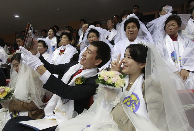 A newly-married couple takes pictures before a mass wedding ceremony at the CheongShim Peace World Center in Gapyeong, South Korea, Wednesday, February 12, 2014. (Photo by Lee Jin-man/AP Photo)