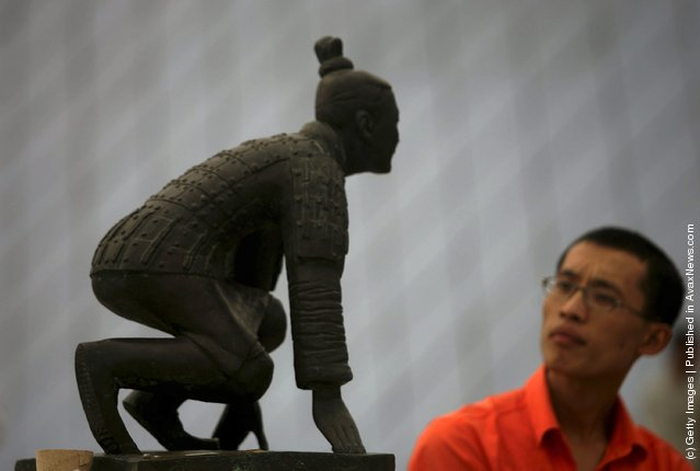 A visitor views the sculpture New Beijing, New Starting Point at the Olympic Sculptures Exhibition at Window of the World theme park
