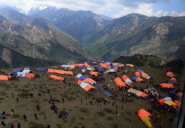 "Nepalese villagers walks near their makeshifts tents at Laprak village in Gorkha district in Nepal on May 4, 2015. US transport aircraft were due to make ""an immediate difference"" to the aid effort in Nepal May 4, shuttling supplies and rescue teams to remote areas devastated by an earthquake that killed more than 7,300 people. (Photo by Sajjad Hussain/AFP Photo)"