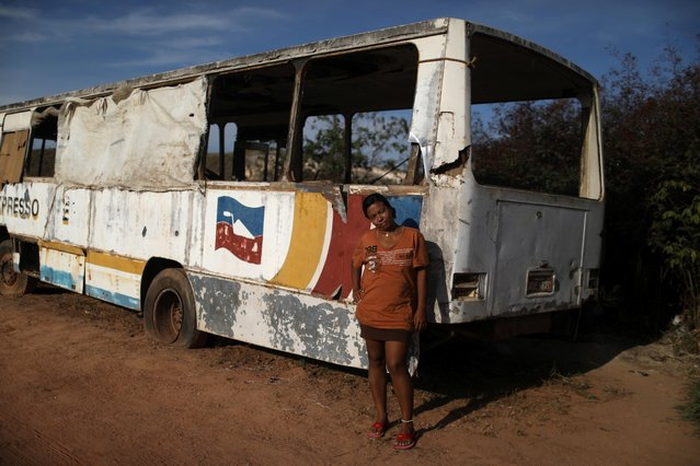"Venezuelan Ixora Sanguino, who was a student in her country, poses outside of an abandoned bus in the border city of Pacaraima, Brazil on April 13, 2019. Sanguino, 27, sweeps the floor of the bus and folds the blankets. ""I never thought I would ever live in a bus, and least of all in another country like this"", said the mother of three who had to leave her children behind in Ciudad Bolivar. ""There is nothing in Venezuela right now"", she said. When she first crossed the border, Sanguino slept in the street. The bus is an improvement, sheltered from tropical rain. Now she is trying to gather enough money for a bus ticket to Boa Vista, the nearest Brazilian state capital, to find work and send cash to her hungry family back home. (Photo by Pilar Olivares/Reuters)"