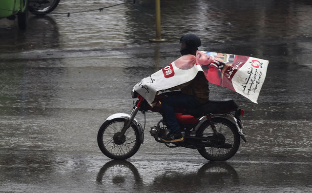 A Pakistani man wears a poster to protect himself from the rain as he rides his motorbike on a road in Lahore on January 31, 2019. (Photo by Arif Ali/AFP Photo)