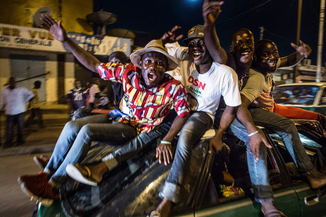 Supporters of Incumbent President Denis Sassou Nguessu celebrate in the streets of Brazzaville after informations of an early lead in the electoral results spread through the city on March 22, 2016. Congo's veteran leader Denis Sassou Nguesso has secured 67 percent of votes in his bid to extend his 32-year-old rule, partial results showed Tuesday, after a tense weekend poll. The results covered 69 percent of the total electorate, the chief of the electoral commission Henri Bouka said, adding that they did not cover Pointe-Noire, the economic capital and opposition stronghold. (Photo by Marco Longari/AFP Photo)