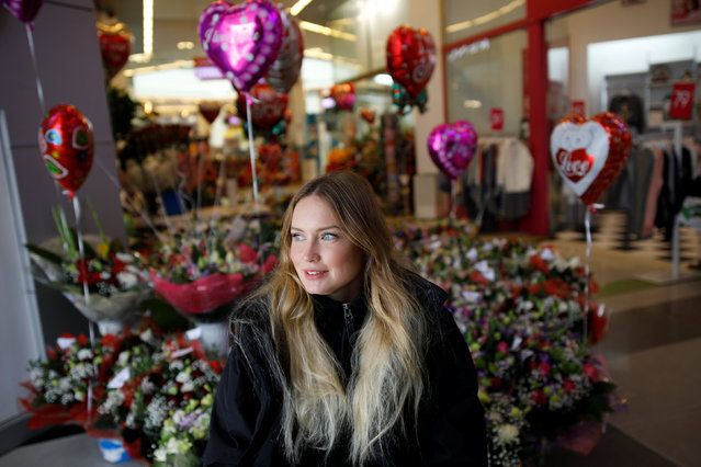 A female security guard sits next to flowers displayed at a shop inside a shopping mall, ahead of Valentine's Day, in Ashkelon, southern Israel February 13, 2017. (Photo by Amir Cohen/Reuters)