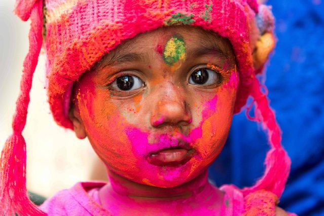 A young Indian reveller covered in coloured powder poses during the Holi Festival in Jaisalmer on March 24, 2016. Holi, also called the Festival of Colours, is a popular Hindu spring festival observed in India at the end of the winter season on the last full moon day of the lunar month. (Photo by Francois Xavier Marit/AFP Photo)