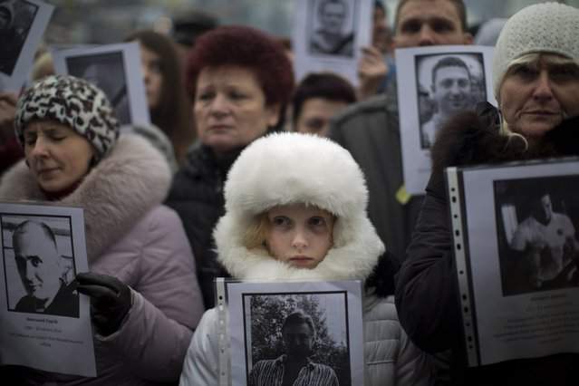 "People hold photos of their relatives killed during recent clashes, during a rally in Kiev's Independence Square, Ukraine, Sunday, March 2, 2014. Ukraine's new prime minister urged Russian President Vladimir Putin to pull back his military Sunday in the conflict between the two countries, warning that ""we are on the brink of disaster"". (Photo by Emilio Morenatti/AP Photo)"