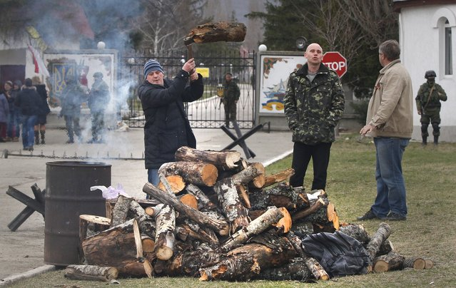 Local residents chopping wood for a bonfire as Russian soldier guards the gate of an Ukrainian infantry base in Perevalne, Ukraine, Tuesday, March 4, 2014.   Tensions remained high in the strategic Ukrainian peninsula of Crimea with troops loyal to Moscow firing warning shots to ward off protesting Ukrainian soldiers. (Photo by Sergei Grits/AP Photo)
