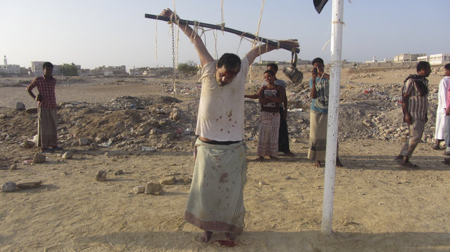 The body of a man is seen tied to a soccer goal post after al Qaeda militants shot him to death accusing him of spying for the United States outside al-Shihr city of the southeastern Yemeni province of Hadhramout March 6, 2014. The militants accused the man, whose identity is unkonwn, of placing microchips in cars and safe houses used by al Qaeda members to guide missiles fired by U.S. drones, local media reported. (Photo by Reuters)